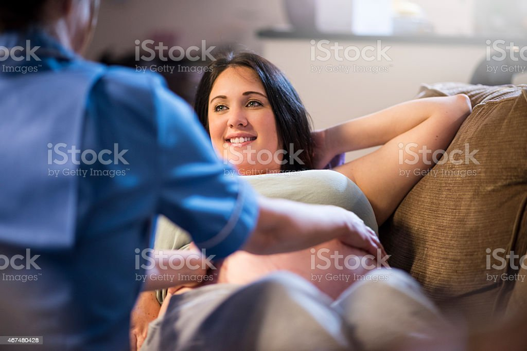 Midwife examining pregnant patients abdomen during home visit stock photo