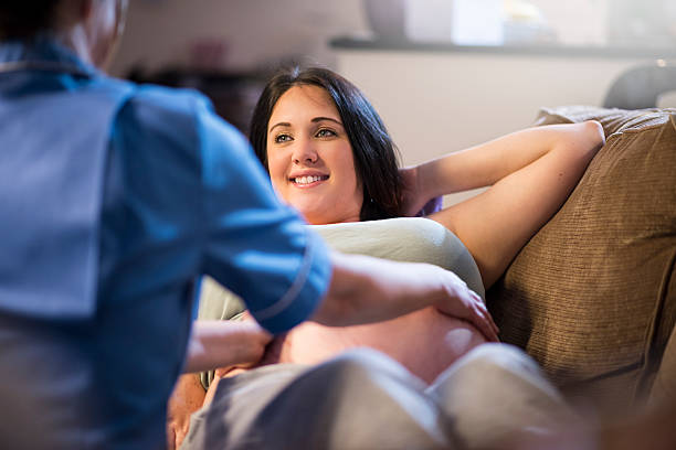 midwife examining pregnant patients abdomen during home visit - midwife stock pictures, royalty-free photos & images