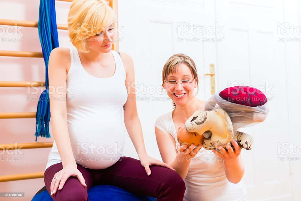 Midwife giving prenatal care for pregnant mother stock photo