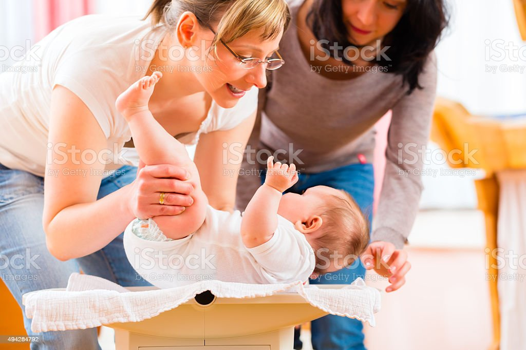 Midwife measuring weight or newborn baby stock photo
