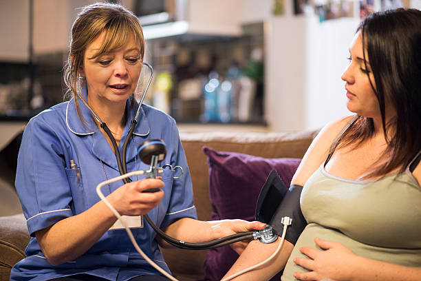 midwife takes patients blood pressure on home visit - midwife stock pictures, royalty-free photos & images