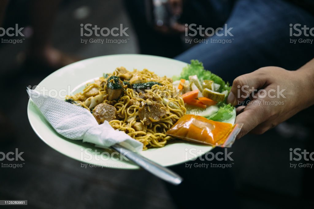 Mie Goreng served with chili sauce and cutlery from street night market in Jakarta, Indonesia. stock photo