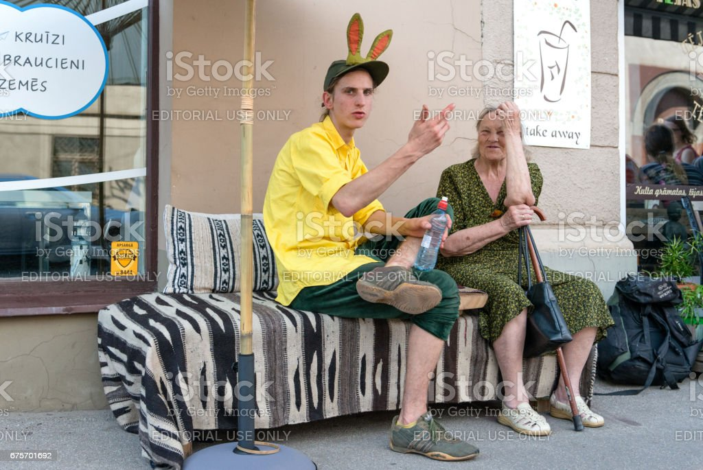 Miera 街五旬節。未知的人坐在路邊,和談了。 免版稅 stock photo