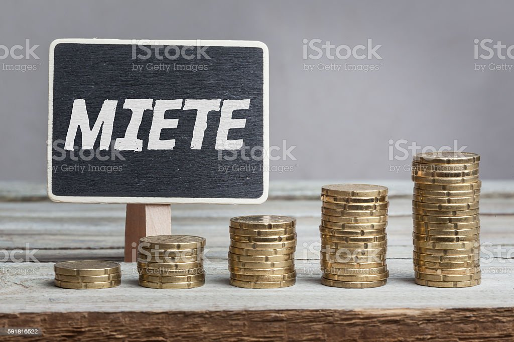 Miete (rent) in German, chalk blackboard and money stacks stock photo