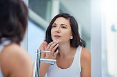 Shot of an attractive young woman inspecting her face in the bathroom mirror