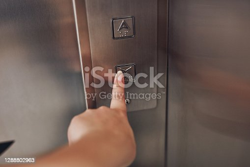 Cropped shot of a woman pressing a button in an elevator