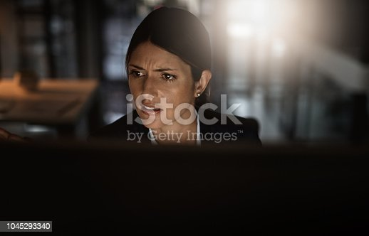 Shot of a young businesswoman experiencing stress during a late night in a modern office