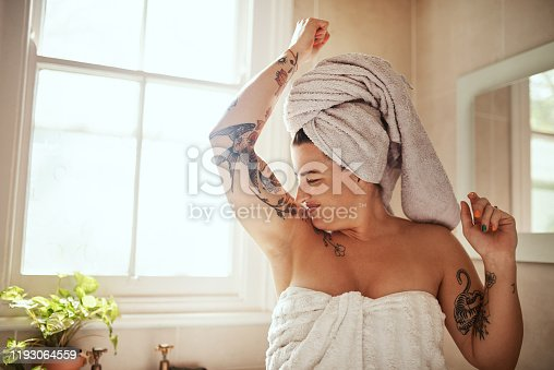 Shot of an attractive young woman smelling her armpits during her morning beauty routine