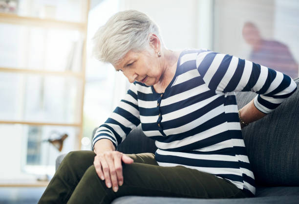 I might need to see a chiropractor Shot of a senior woman experiencing back pain at home bad posture stock pictures, royalty-free photos & images
