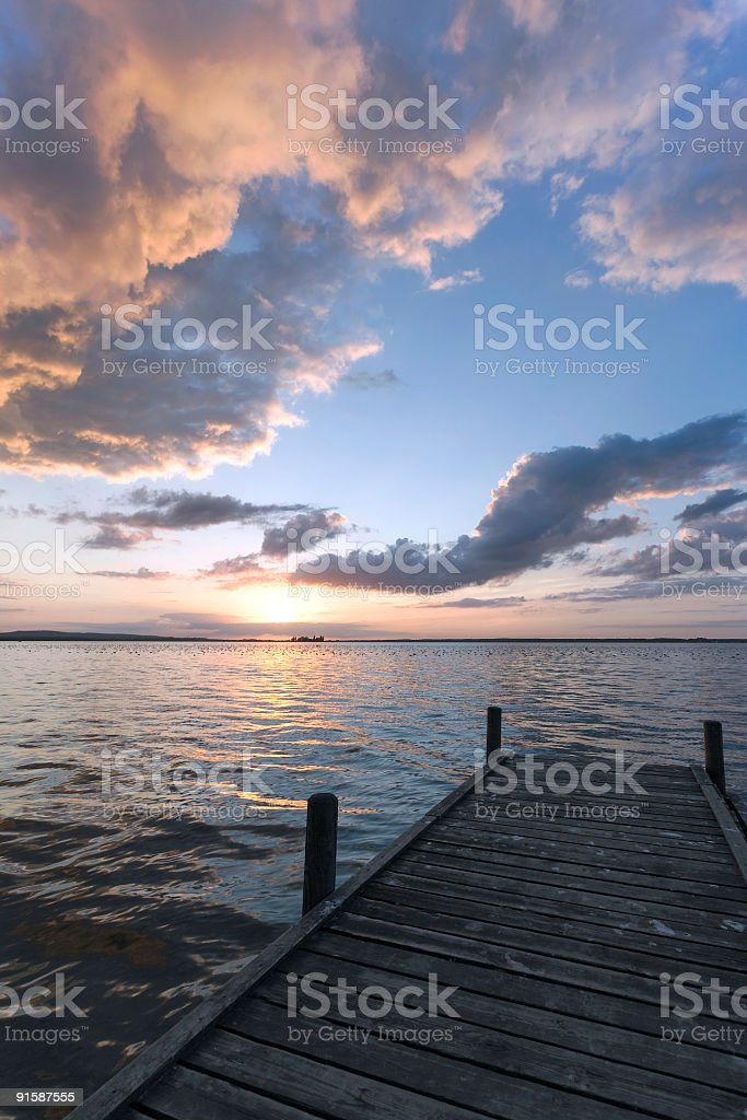 Mighty cloudscape and lakeside jetty at sunset (XL) royalty-free stock photo