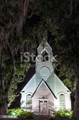 Mighty Oak Trees dripping with Spanish Moss protect this historic white clapboard church