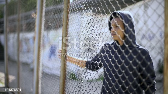 istock Migrant child separated from family, afro-american boy behind fence, detained 1124376321