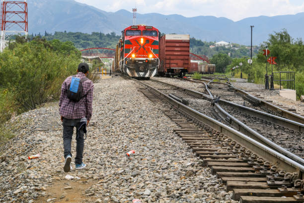 "A migrant along the train line to the border between Mexico and the United States Coahuila, Mexico, Jul 26 - A migrant of Central American origin waits on the railway line to get on a container train, known as ""The Beast"", to reach the border line between the United States and Mexico. frontier field stock pictures, royalty-free photos & images"