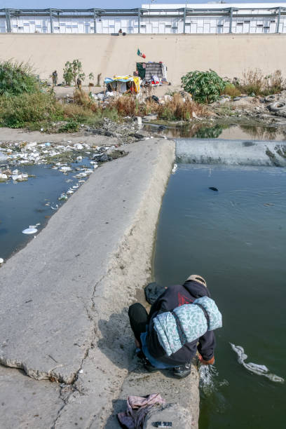 A migrant washes his clothes in a Tijuana canal near the US-Mexico border Tijuana, Mexico, Nov 10 - A Central American and Mexican migrant lives in a Tijuana canal near the iron and steel wall that borders and protects the US-Mexican border, waiting to cross the border. Behind, on the top of the canal, is the boundary wall line. In the foreground a migrant washes his clothes in the canal water. frontier field stock pictures, royalty-free photos & images
