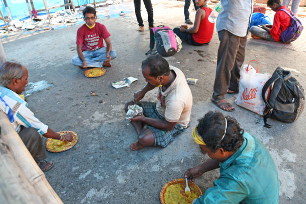 Migrant workers stranded in other states due to lockdown in the emergence of Novel Coronavirus are being provided food by the Burdwan municipality after returning to their home states Burdwan Town, Purba Bardhaman District, West Bengal / India - May 30, 2020: Migrant workers stranded in other states due to lockdown in the emergence of Novel Coronavirus (COVID-19) are being provided food by the Burdwan municipality after returning to their home states. migrant worker stock pictures, royalty-free photos & images