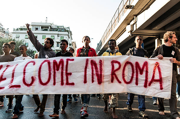 Migrants in Bare feet holding banner at march in rome stock photo