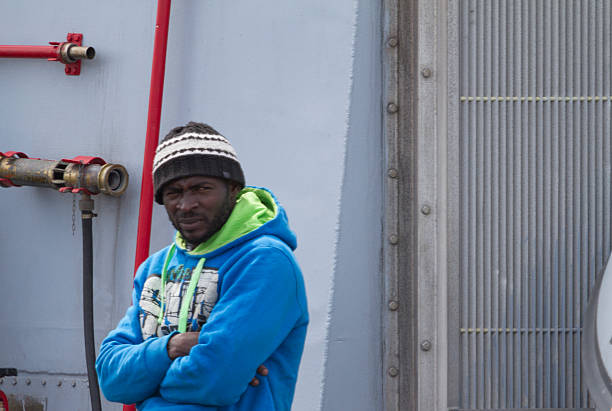 Migrants rescued  wait being processed by Italian authorities. stock photo
