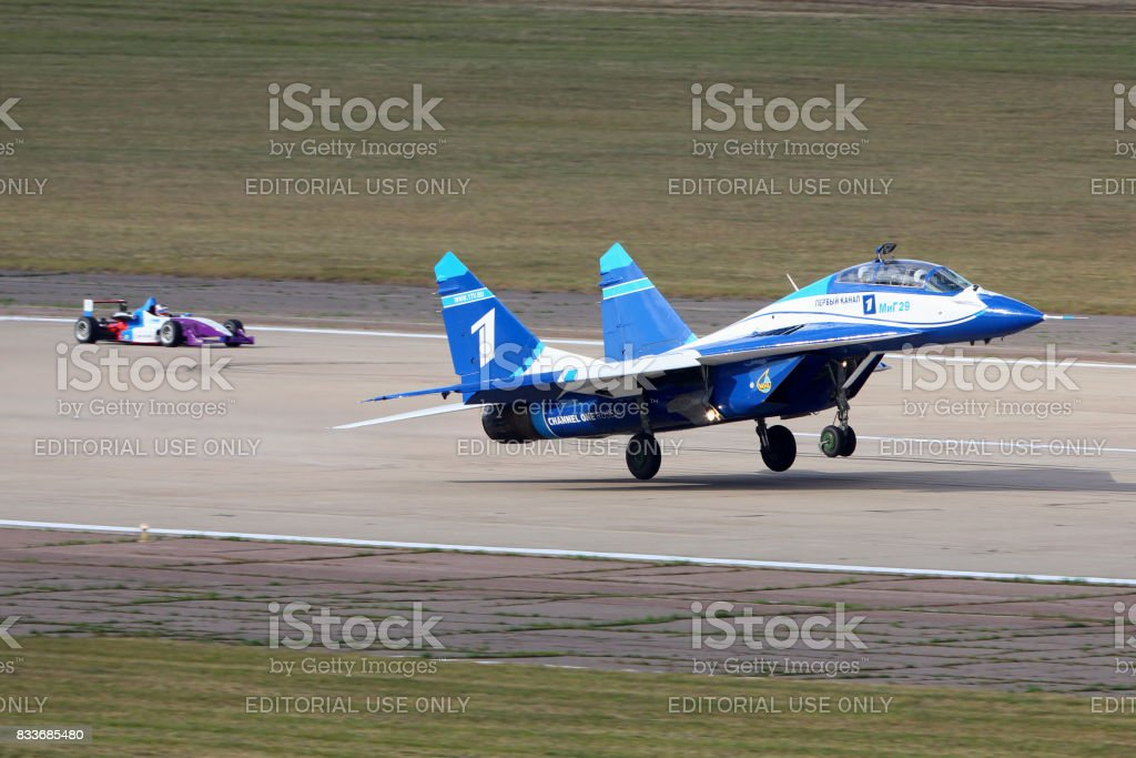 Mikoyan Gurevich MiG-29UB 1 WHITE of russian air force perfoming race with Formula 3 car in Zhukovsky during MAKS-2015 airshow. stock photo