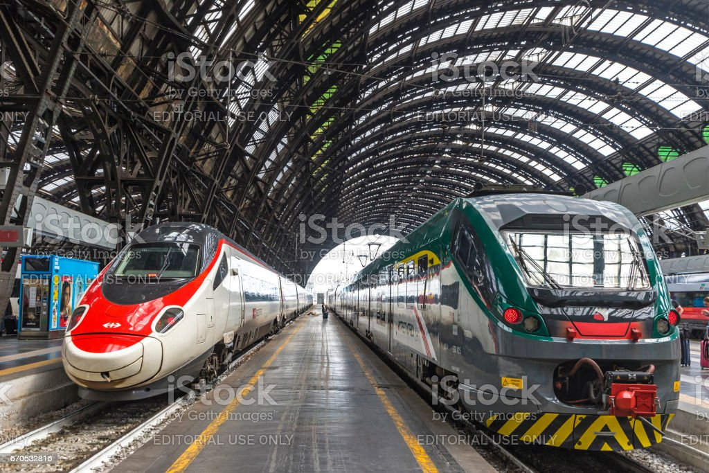 Milan Central Railway Station (Milano Centrale), Italy MILAN, ITALY - JUNE 14, 2016: Train SBB (Left) and Trenord companies on platforms of the Milan Central Railway Station (Milano Centrale). It is the main railway station of Milan, Italy. Opened in 1931 Architecture Stock Photo