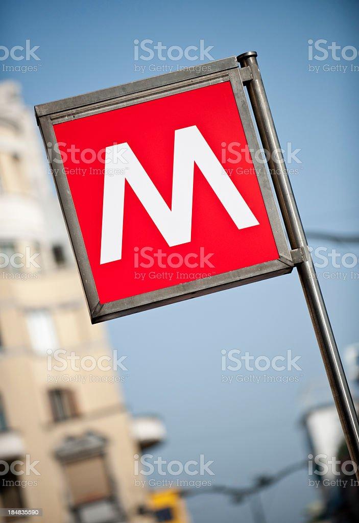 Segno della metropolitana di Milano con appartamento edificio in background - Foto stock royalty-free di Alfabeto