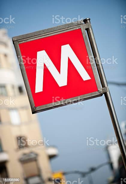 Segno Della Metropolitana Di Milano Con Appartamento Edificio In Background - Fotografie stock e altre immagini di Alfabeto
