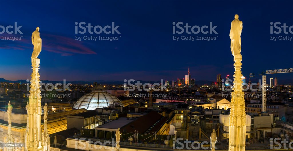 Aerial view of Milan skyline by night from Duomo roof. Spire in the...