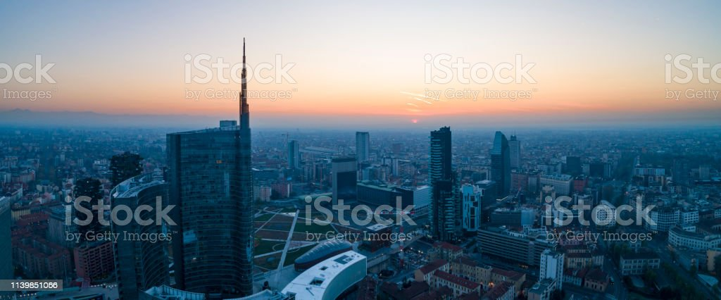 Milan city skyline at dawn, aerial view, flying over financial area...