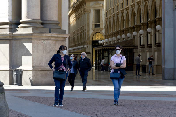 Milan - Two women walk outdoor the Gallery of Vittorio Emanuele wearing medical mask, during coronavirus epidemic period. stock photo