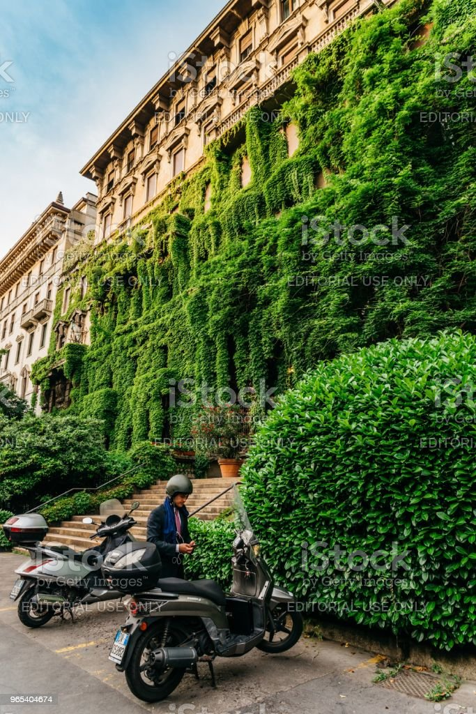 A Milanese man dressed in a suit next to his vespa in front of a palace in Viale Luigi Majno covered in leaves, Lombardy, Italy royalty-free stock photo