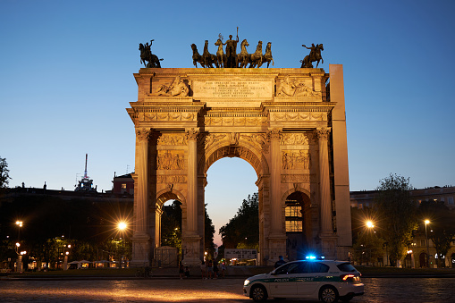 Milano city center arco della pace at sunset monument. A police car is passing by. Milan Italy 08.2020