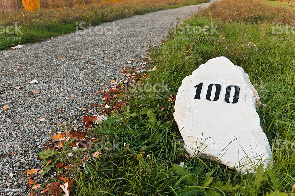 Mile stone in the grass near a road stock photo