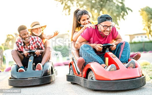 Milenial friends having fun at children playground on go kart race - Young people with face mask competing on mini car racing - New normal lifestyle concept with focus on right guy - Backlight filter