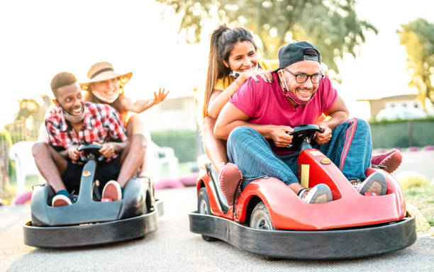 Milenial friends having fun at children playground on go kart race - Young people with face mask competing on mini car racing - New normal lifestyle concept with focus on right guy - Backlight filter stock photo
