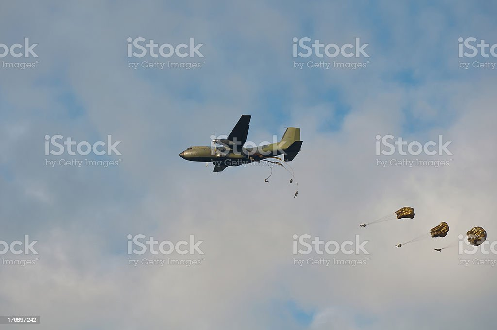 Military aircraft dropping paratroopers stock photo