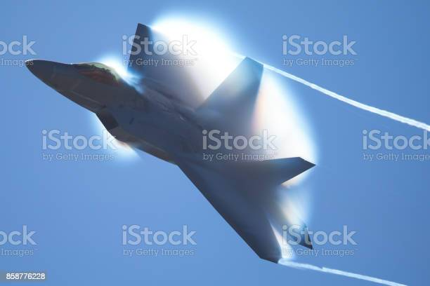 Photo of Military Airplane in a high-G maneuver, with afterburners on, and condensation clouds and streaks around the plane..