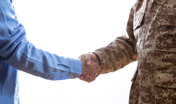 military and civilian shaking hands standing on white background - tropa imagens e fotografias de stock