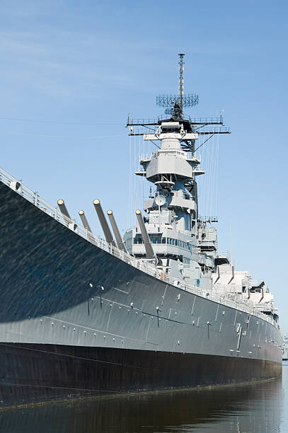 Military Battleship USS Wisconsin, Side View USS Wisconsin battleship of the US Navy tied to the dock in harbor as a tourist attraction, vintage military equipment, Norfolk, Virginia, VA, USA.  naval base stock pictures, royalty-free photos & images