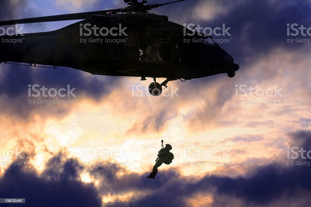 Military blackhawk helicopter rescuing a soldier stock photo