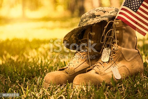 istock USA Military boots, flag, hat, and dog tags outdoors. 953512710