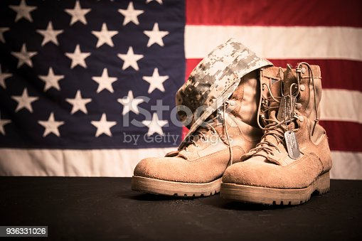 istock USA Military boots, hat and dog tags with flag. 936331026