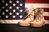 USA military boots, hat and dog tags with American flag in background.  No people in this Memorial Day or Veteran's Day image.