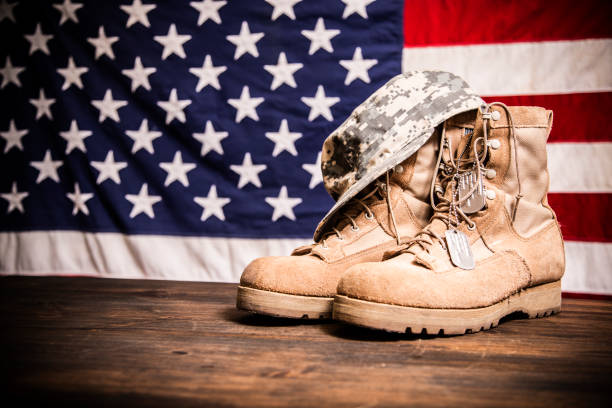 USA Military boots, hat and dog tags with flag. USA military boots, hat and dog tags with American flag in background.  No people in this Memorial Day or Veteran's Day image. us military stock pictures, royalty-free photos & images