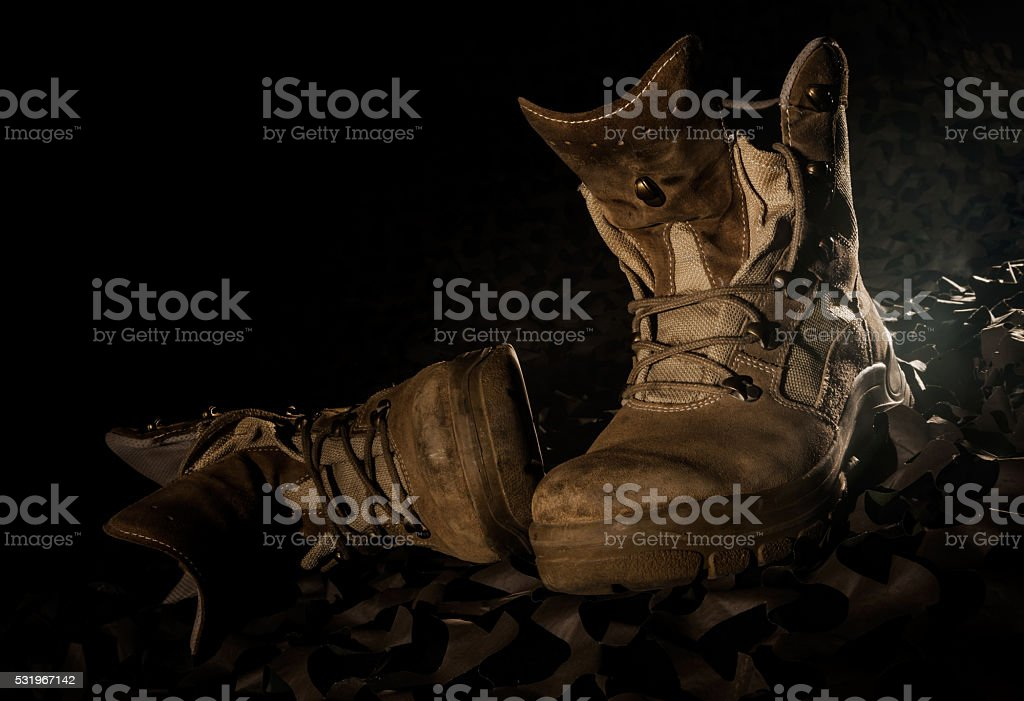 military boots on camouflage net and black backround stock photo