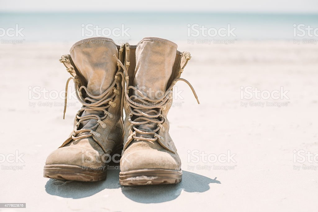 military boots on the sand in the sun stock photo