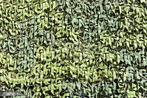 Military camouflage net as background. Green leafs camouflage for texture