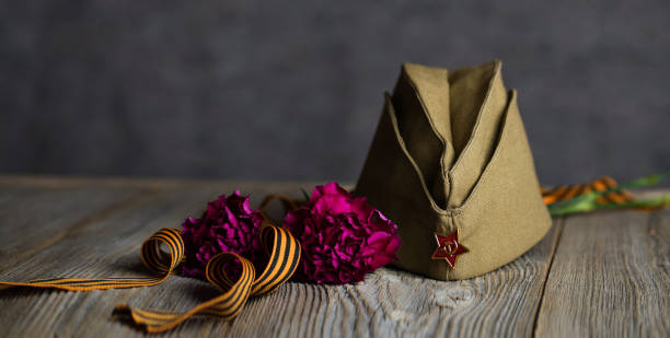 Military cap, carnations, Saint George ribbon on a wooden surface. stock photo