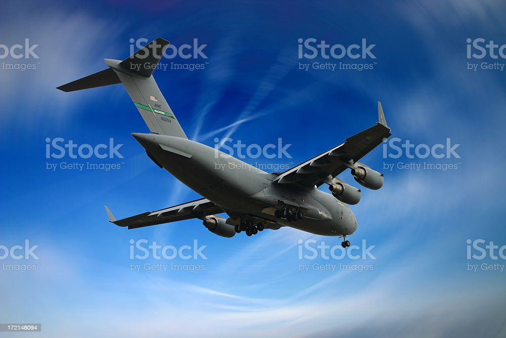 A military cargo plane flying in the blue sky stock photo