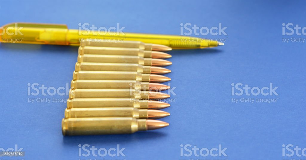 Military Cartridges  5.56mm Ammunition With Pen as a Concept of Propaganda in Mass Media. Fake News Invasion Concept. Ukraine Crisis. Syria War. Tramp and Russia. stock photo