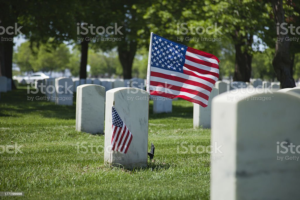 Military cemetery with US flags flying on tombstone royalty-free stock photo