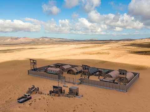 istock Military compound in the middle east, aerial view of a military base. Guard towers and reinforced concrete fence. 1265238555